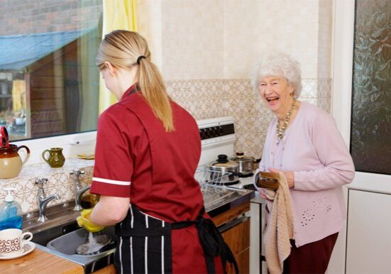 carer helps her elderly pactient by washing the dishes for her